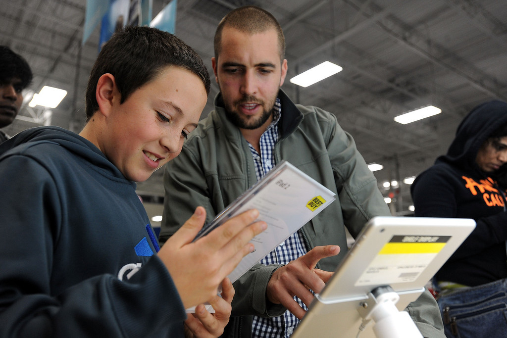 . Sabastian Valenzuela, left, and his older brother Alberto compare prices for iPad tablets at a Best Buy late in the evening on Thanksgiving Day, Thursday, Nov. 28, 2013, in Dunwoody, Ga. Instead of waiting for Black Friday, which is typically the year\'s biggest shopping day, more than a dozen major retailers opened on Thanksgiving this year. (AP Photo/David Tulis)