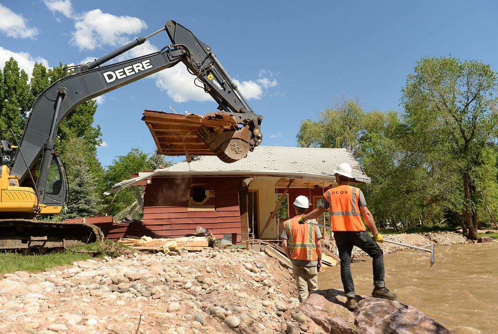 . Crews with Ecoos Environmental and Disaster Restoration work on demolishing a home in Lyons that was damaged by last years flood, May 27, 2014. (Photo by RJ Sangosti/The Denver Post)