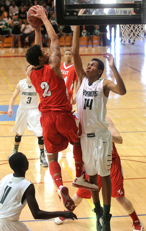 . DENVER, CO. - FEBRUARY 16: Patriots defender Elijah Hewlett (14) went for the block on Angels guard Jevon Griffin (2) as he drove the baseline in the first half. The Denver East High School boy\'s basketball team defeated George Washington 82-20 Saturday afternoon, February 16, 2013.  (Photo By Karl Gehring/The Denver Post)