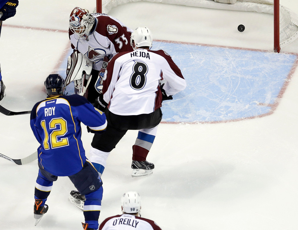 . St. Louis Blues\' Derek Roy (12) scores past Colorado Avalanche goalie Jean-Sebastien Giguere and Jan Hejda (8), of the Czech Republic, during the first period of an NHL hockey game Thursday, Nov. 14, 2013, in St. Louis. (AP Photo/Jeff Roberson)