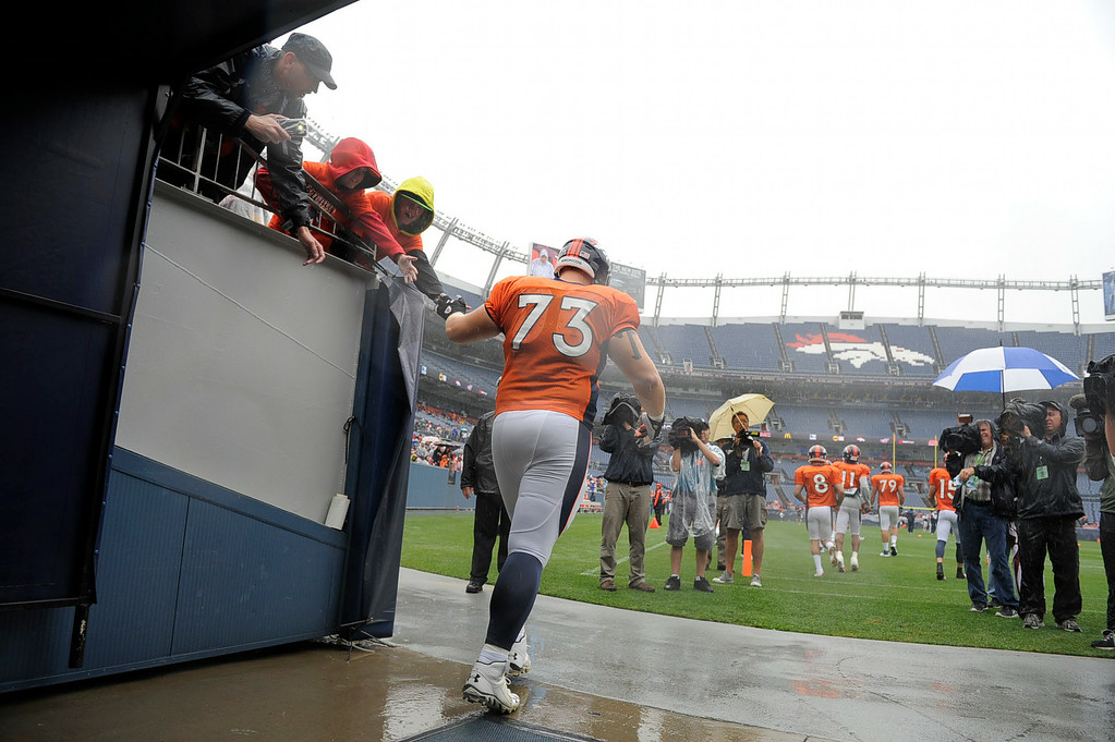 . Denver Broncos offensive guard Ryan Miller (73) high fives fans as he takes the field during day six of the  Denver Broncos 2014 training camp July 30, 2014 at Sports Authority Field at Mile High Stadium.  (Photo by John Leyba/The Denver Post)