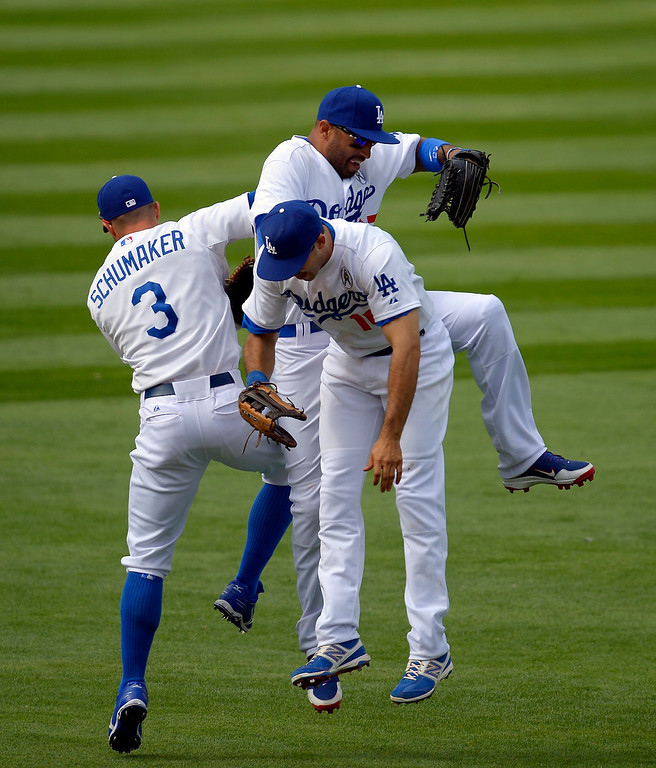 . Los Angeles Dodgers second baseman Skip Schumaker, left, center fielder Matt Kemp, top, and right fielder Andre Ethier celebrate after they defeated the San Francisco Giants in their opening day baseball game at Dodger Stadium, Monday, April 1, 2013, in Los Angeles. The Dodgers won 4-0. (AP Photo/Mark J. Terrill)