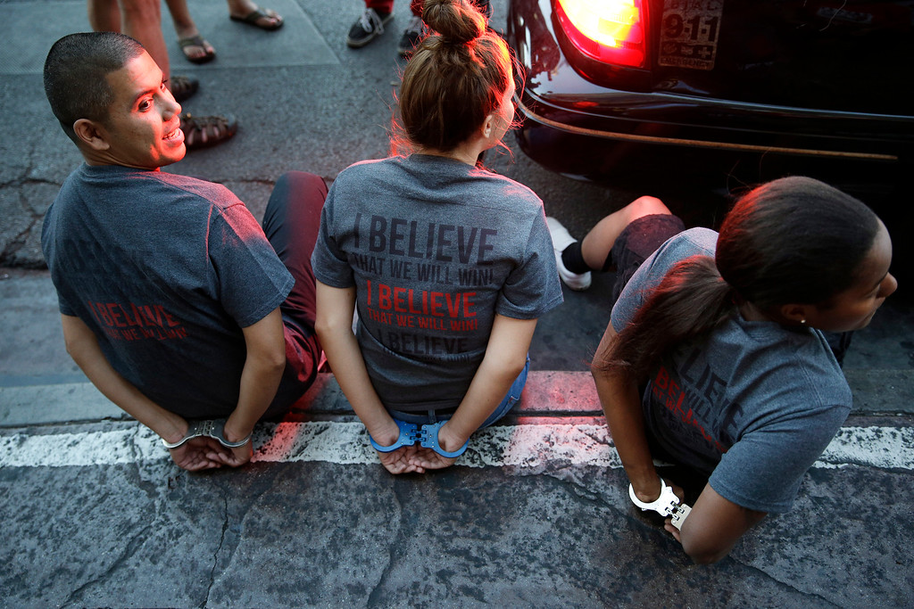 . Handcuffed protestors sit on a curb Thursday, Sept. 4, 2014, in Las Vegas. Police detained several protesters in cities nationwide Thursday as they blocked traffic in the latest attempt to escalate their efforts to get McDonald\'s, Burger King and other fast-food companies to pay their employees at least $15 an hour. (AP Photo/John Locher)