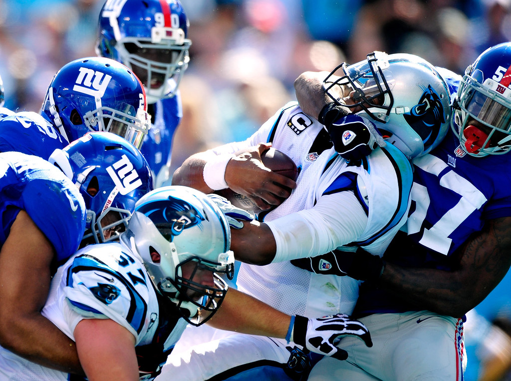 . Cam Newton #1 of the Carolina Panthers drives Jacquian Williams #57 of the New York Giants across the goal line for a touchdown during play at Bank of America Stadium on September 22, 2013 in Charlotte, North Carolina. The Panthers won 38-0.  (Photo by Grant Halverson/Getty Images)