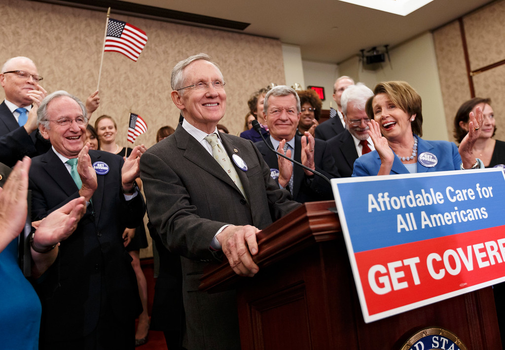 . Senate Majority Leader Harry Reid of Nev., center, accompanied by other lawmakers and people who\'s lives have been impacted by lack of health insurance, smiles during a news conference on Capitol Hill in Washington, Tuesday, Oct. 1, 2013, to celebrate the first day of the Affordable Care Act, popularly known as Obamacare. From left are, Sen. Tom Harkin, D-Iowa, Reid, Sen. Max Baucus, D-Mont. and House Minority Leader Nancy Pelosi of Calif.    (AP Photo/J. Scott Applewhite)