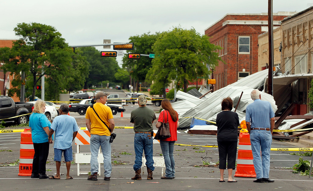 . People check out the damage to downtown Ennis, Texas on Thursday, May 16, 2013.   (AP Photo/The Dallas Morning News, Vernon Bryant)