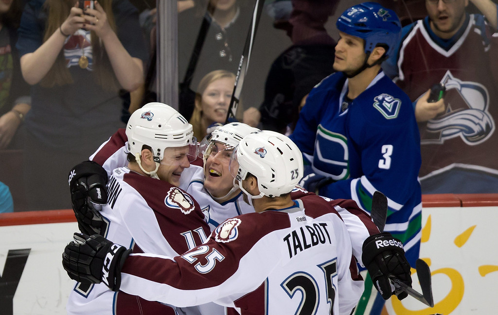 . Colorado Avalanche\'s Jamie McGinn, Tyson Barrie and Maxime Talbot. from left, celebrate Barrie\'s goal as Vancouver Canucks\' Kevin Bieksa skates past during the third period of an NHL hockey game Thursday, April 10, 2014, in Vancouver, British Columbia. (AP Photo/The Canadian Press, Darryl Dyck)