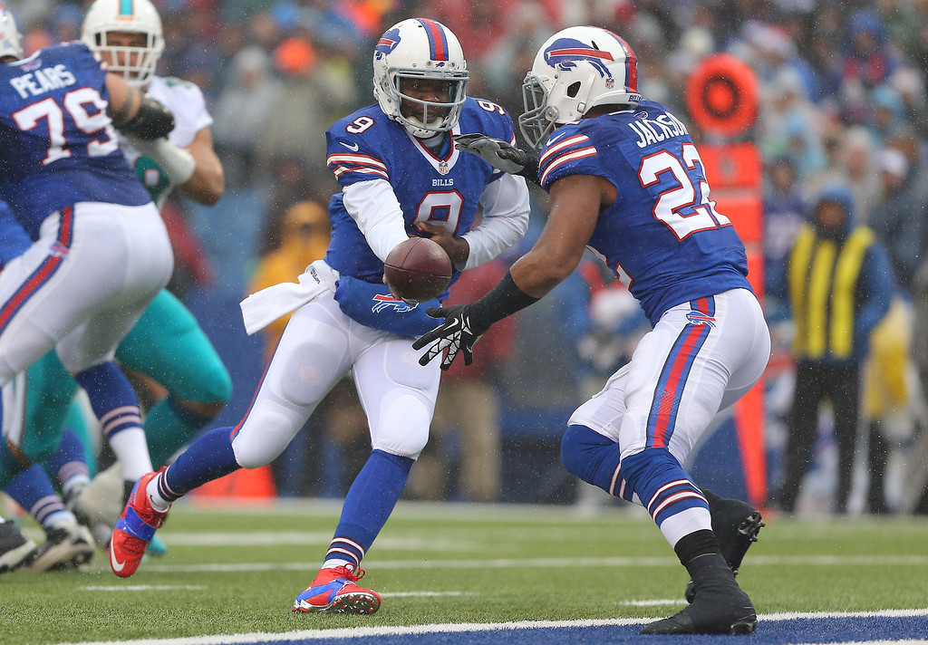 . Thad Lewis #9 of the Buffalo Bills hands the ball off to Fred Jackson #22 during NFL game action against the Miami Dolphins at Ralph Wilson Stadium on December 22, 2013 in Orchard Park, New York. (Photo by Tom Szczerbowski/Getty Images)
