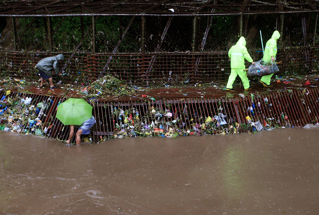 . Members of the Baguio City Disaster Risk Reduction Management Council and local police clean up the screen of the City Camp Lagoon Tunnel in Baguio city, as powerful typhoon Utor batters the northern Philippines on Monday Aug. 12, 2013, toppling power lines and dumping heavy rain across mountains, cities and food-growing plains. The storm killed at least one man in a landslide and left 45 fishermen missing. Typhoon Utor, described as the strongest globally so far this year, slammed ashore in mountainous eastern Aurora province with sustained winds of 175 kilometers (109 miles) per hour and gusts of up to 210 kph (130 mph). (AP Photo)