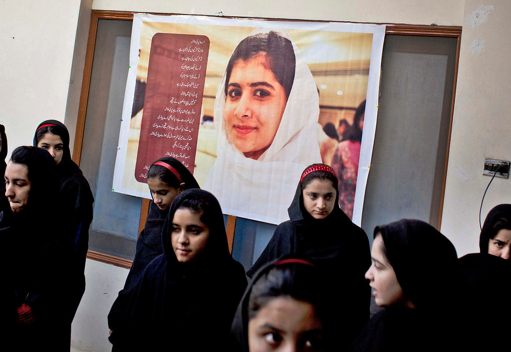 . Pakistani girls gather under a poster of Malala Yousufzai in her old school in Mingora, Swat Valley, Pakistan on Thursday, Nov. 15, 2012. The giant poster of her that once emblazoned the wall of the assembly hall has been removed. The school made no plans to recognize the anniversary of Malala\'s shooting by Taliban because teachers and students are afraid.  (AP Photo/Anja Niedringhaus)