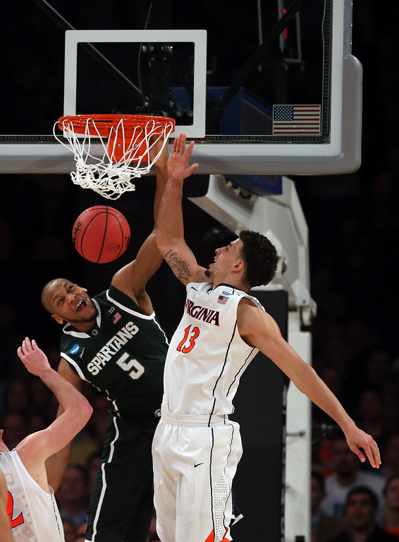 . Adreian Payne #5 of the Michigan State Spartans dunks the ball over Anthony Gill #13 of the Virginia Cavaliers during the regional semifinal of the 2014 NCAA Men\'s Basketball Tournament at Madison Square Garden on March 28, 2014 in New York City.  (Photo by Bruce Bennett/Getty Images)