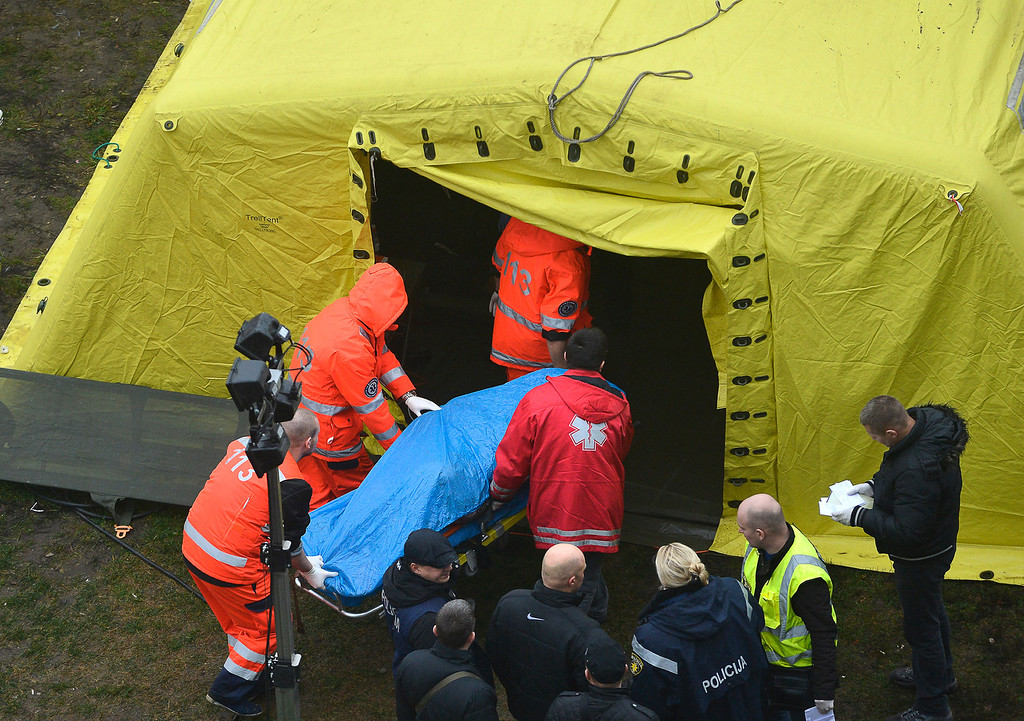 . Rescue workers carry a stretcher with a victim\'s body outside the Maxima supermarket in Riga, Latvia, Friday, Nov 22, 2013.  (AP Photo/Maris Morkans)