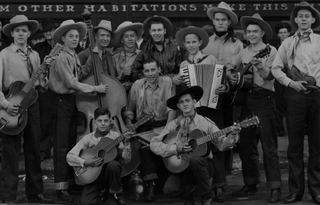 . The Raton High School Hillbillies, from Raton N.M., visited the Denver Post  and played a concert in Champa street, to the delight of a larger crowd. They were here for the Stock show. Their sponsor and director, Perry W. Knight is standing back row, third from the left. The Hillbillies play for dances in and around Raton. The Denver Post enjoyed their snappy tunes. 1940. Denver Post Library photo archive