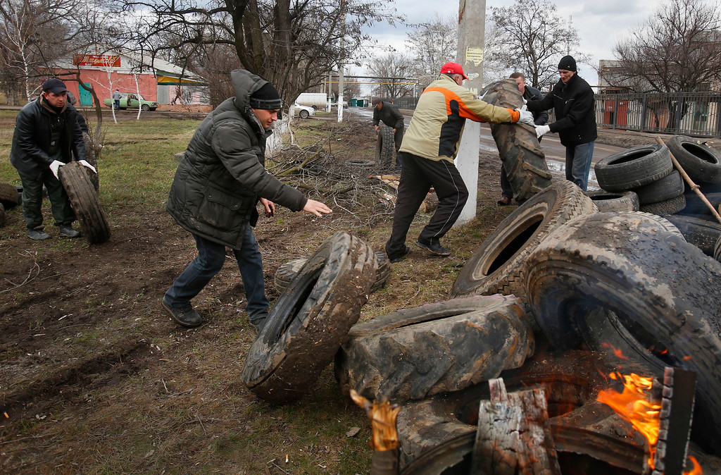 . Pro Russian activists block a road with car tires near the armory Ukrainian army to prevent the export of arms and ammunition in the village of Poraskoveyevka, eastern Ukraine, Thursday, March 20, 2014. The disheveled men barricading the muddy lane leading into a military base in this eastern Ukraine village say they\'re taking a stand to defend Russian-speakers. (AP Photo/Sergei Grits)