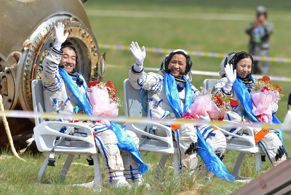. Chinese astronauts (L-R) Zhang Xiaoguang, Nie Haisheng and Wang Yaping wave after getting out from the return capsule of the Shenzhou-10 spacecraft after it landed in the grasslands of north China\'s Inner Mongolia region on June 26, 2013 following a 15-day mission in space. China completed its longest manned space mission on June 26 as its Shenzhou-10 spacecraft and three crew members safely returned to Earth, in a major step towards Beijing\'s goal of building a permanent space station by 2020.  AFP PHOTOAFP/AFP/Getty Images