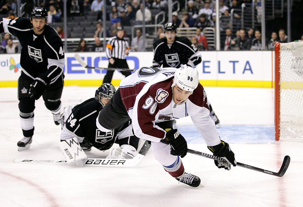 . Colorado Avalanche\'s Ryan O\'Reilly, right, falls to the ice as he goes after the puck during the first period of an NHL hockey game against the Los Angeles Kings on Saturday, Nov. 23, 2013, in Los Angeles. (AP Photo/Jae C. Hong)