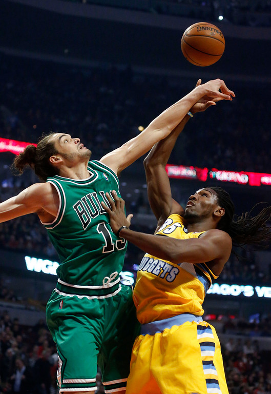 . Chicago Bulls center Joakim Noah (13) blocks the shot of Denver Nuggets forward Kenneth Faried during the first half of an NBA basketball game, Monday, March 18, 2013, in Chicago. (AP Photo/Charles Rex Arbogast)