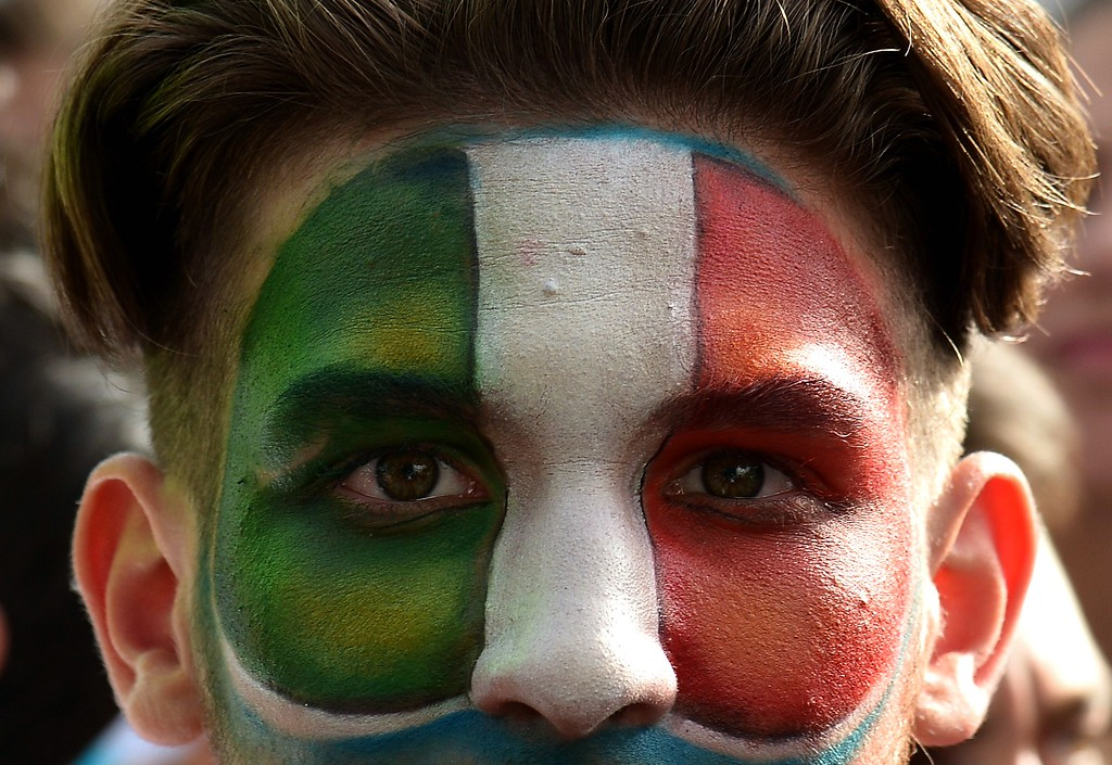 . An Italy fan with his face painted in the colors of the Italian flag watches the FIFA World Cup 2014 Group D football match Italy vs Uruguay on a giant screen in central Rome on June 24 , 2014. AFP PHOTO / ALBERTO  PIZZOLI/AFP/Getty Images