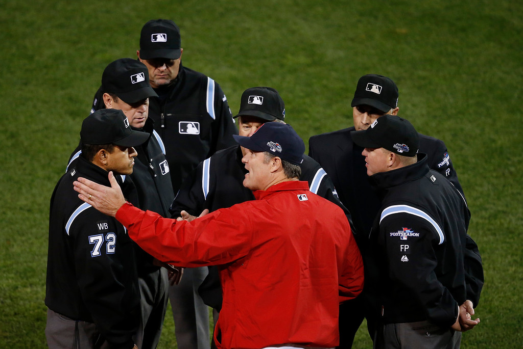 . Boston Red Sox manager John Farrell, center, talks to the umpire crew after a long foul ball by Red Sox\'s Dustin Pedroia during the third inning in Game 6 of the American League baseball championship series against the Detroit Tigers on Saturday, Oct. 19, 2013, in Boston.  (AP Photo/Elise Amendola)