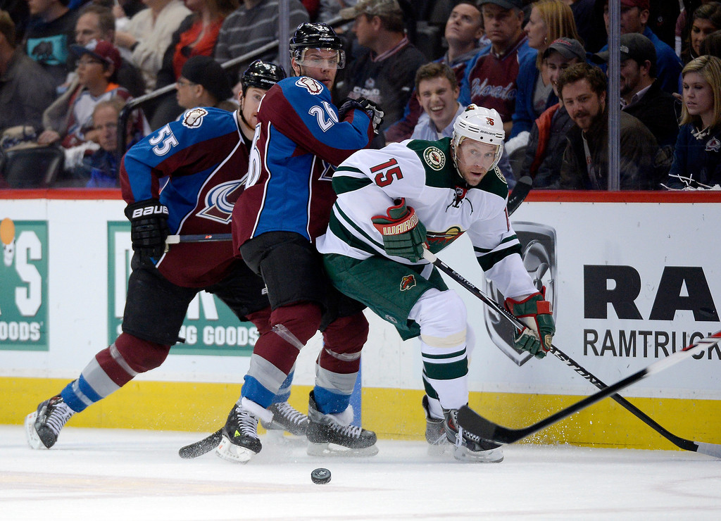 . Minnesota Wild left wing Dany Heatley (15) takes the puck from Colorado Avalanche center Paul Stastny (26) and Colorado Avalanche left wing Cody McLeod (55) against the boards during the first period.   (Photo by John Leyba/The Denver Post)