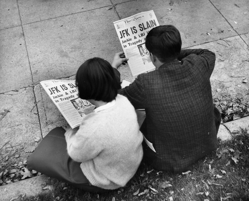 . Two people in Washington, D.C.\'s Lafayette Park read coverage of the Kennedy assassination on Nov. 25, 1963. Keystone/Getty Images