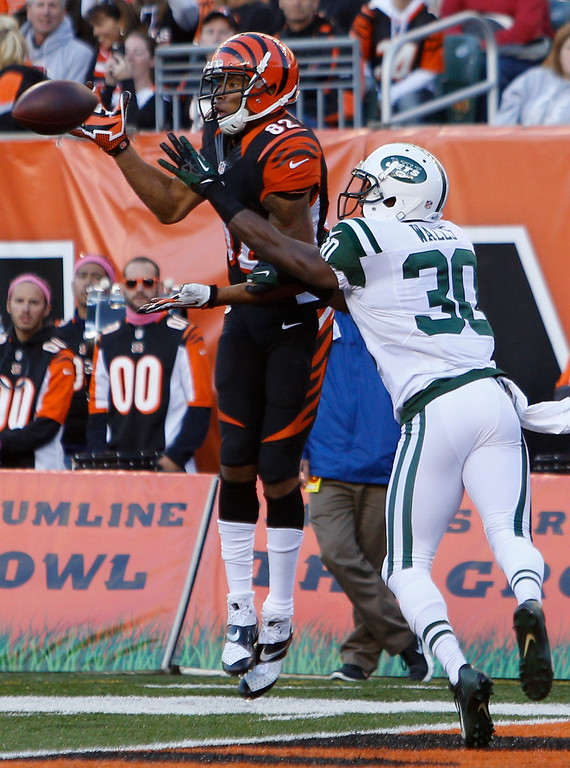 . Cincinnati Bengals wide receiver Marvin Jones (82) catches an eight-yard touchdown pass against New York Jets cornerback Darrin Walls (30) in the first half of an NFL football game, Sunday, Oct. 27, 2013, in Cincinnati. (AP Photo/David Kohl)