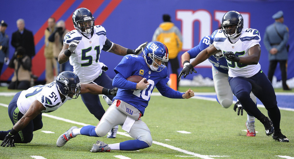 . New York Giants quarterback Eli Manning (10) slides down to avoid being hit by Seattle Seahawks middle linebacker Bobby Wagner (54), outside linebacker Bruce Irvin (51) and defensive end Cliff Avril (56) during the first half of an NFL football game, Sunday, Dec. 15, 2013, in East Rutherford, N.J. (AP Photo/Bill Kostroun)