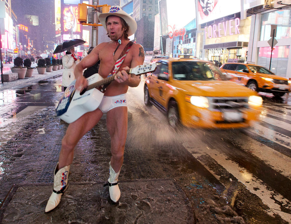 ". Robert Burck, aka the ""Naked Cowboy,\"" performs in Times Square as it snows Friday, Feb. 8, 2013, in New York. Snow began falling across the Northeast on Friday, ushering in what was predicted to be a huge, possibly historic blizzard and sending residents scurrying to stock up on food and gas up their cars. The storm could dump 1 to 3 feet of snow from New York City to Boston and beyond.  (AP Photo/Frank Franklin II)"