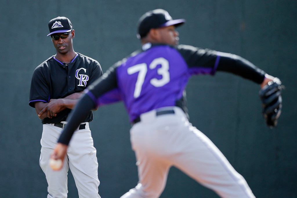 . Colorado Rockies starting pitcher LaTroy Hawkins, left, watches as pitcher Jayson Aquino, right, throws during a spring training baseball practice, Friday, Feb. 21, 2014, in Scottsdale, Ariz. (AP Photo/Gregory Bull)