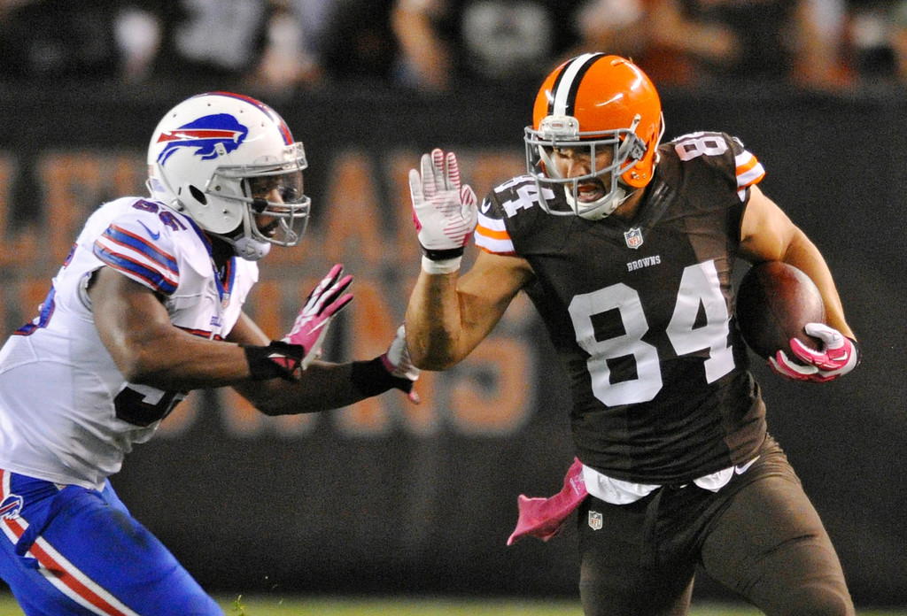 . Cleveland Browns tight end Jordan Cameron (84) looks to fend off Buffalo Bills outside linebacker Jerry Hughes on a reception good for a first down in the second quarter of an NFL football game Thursday, Oct. 3, 2013, in Cleveland. (AP Photo/David Richard)