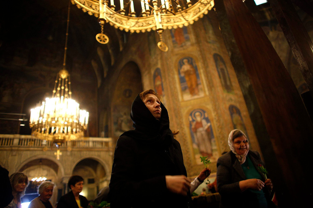 ". A worshipper looks at a wooden cross during the Good Friday mass at ""Alexander Nevski\"" cathedral in Sofia May 3, 2013. Bulgaria and other Eastern Orthodox countries celebrate Easter this weekend.       REUTERS/Stoyan Nenov"