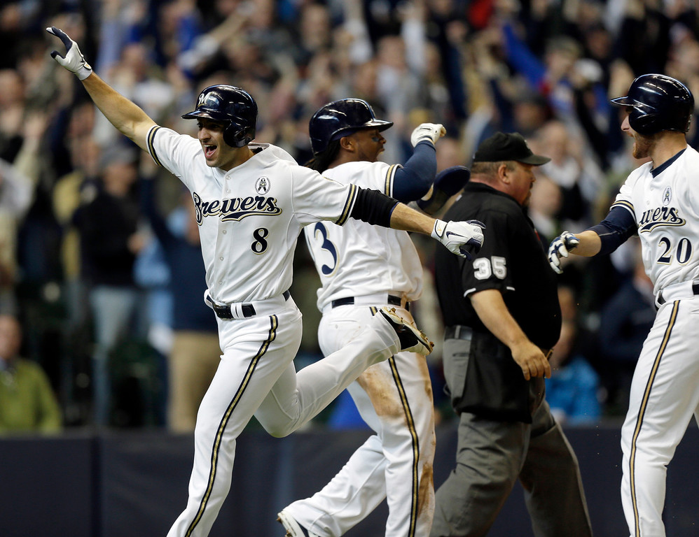 . Milwaukee Brewers\' Ryan Braun, left, Rickie Weeks, and Jonathan Lucroy, right, react after Weeks and Braun scored on Aramis Ramirez\'s  two-run double against the Colorado Rockies in the eighth inning of an opening day baseball game  Monday, April 1, 2013, in Milwaukee. (AP Photo/Jeffrey Phelps)