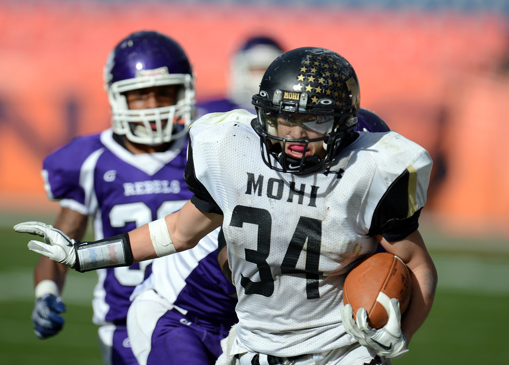 . Monarch RB Logan Soole (34) controls the ball against Denver South defense during 4A State Championship game at Sports Authority Field at Mile High on Saturday, Dec. 1, 2012. Monarch won 17-14. Hyoung Chang, The Denver Post