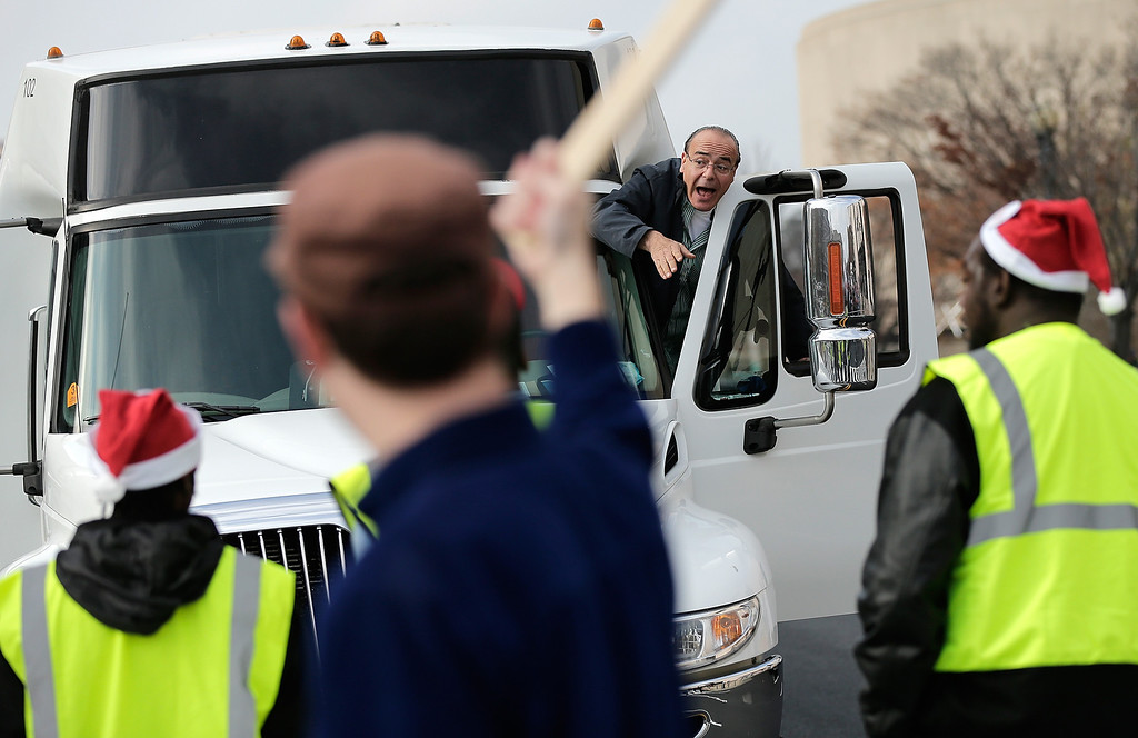 . A bus driver shouts at low wage workers and supporters of an increase in the minimum wage as they block Independence Avenue during a protest outside the Air and Space Museum December 5, 2013 in Washington, DC.  (Photo by Win McNamee/Getty Images)