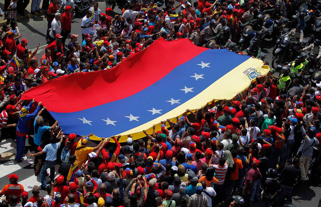 . Supporters of Venezuela\'s late President Hugo Chavez stretch out a large national flag as they gather to see his coffin driven through the streets of Caracas, March 6, 2013.      REUTERS/Jorge Dan Lopez