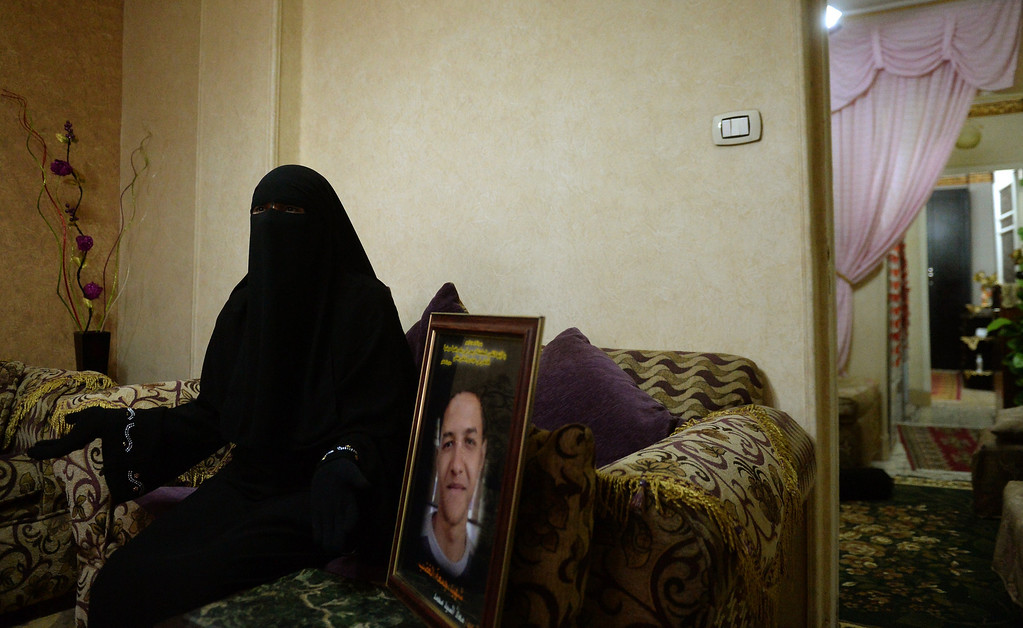 """. A fully-veiled Muslim woman, identified as Um Moaz, sits on August 22, 2013 at home in Cairo next to a picture of her son who was shot dead during the \""""Friday of Rage\""""on January 28, 2011, at the height of the revolution against Egypt\'s deposed president Hosni Mubarak. Um Moaz said she feels that the \""""revolution\"""" as well as her son and all the others who were killed were betrayed following news that the former president was expected to leave the prison following a court order for his conditional release pending trial. The ex-president, who could walk out of prison on August 22, will immediately be placed under house arrest.  MARWAN NAAMANI/AFP/Getty Images"""