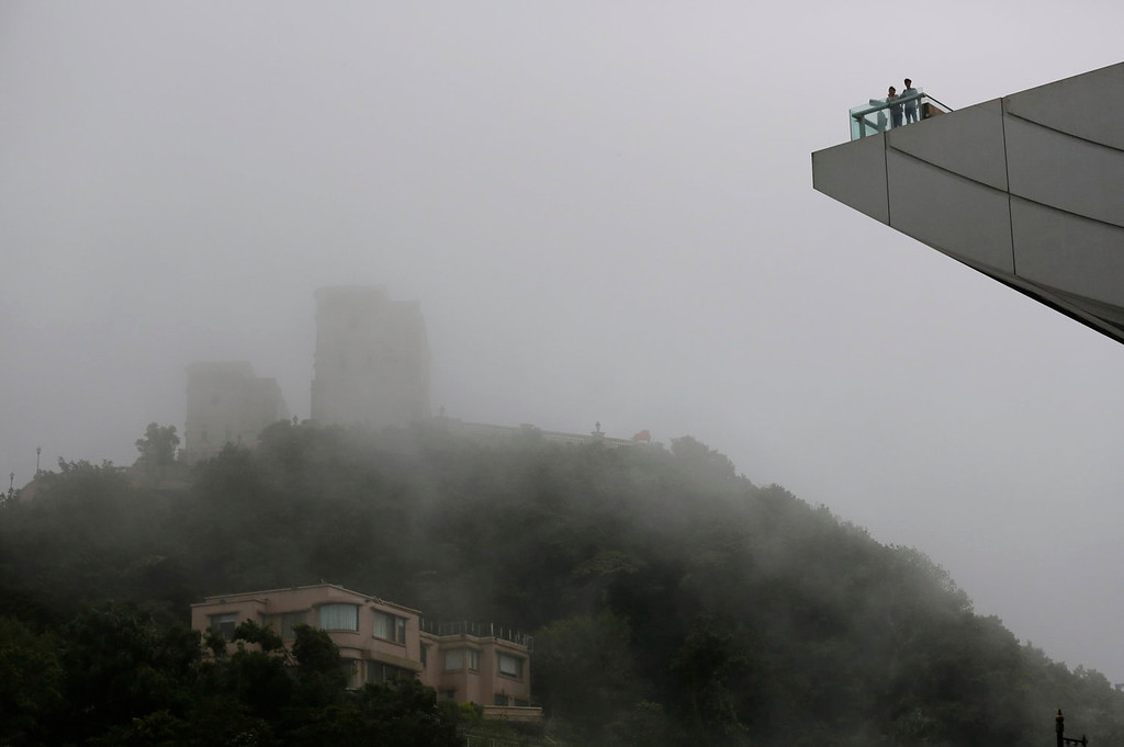 . Tourists visit the Victoria Peak in Hong Kong Tuesday, Aug. 13, 2013. The Observatory said Typhoon Utor intensified slightly as it moves towards the western coast of Guangdong. The typhoon battered the northern Philippines on Monday, toppling power lines and dumping heavy rain across cities and food-growing plains. (AP Photo/Kin Cheung)