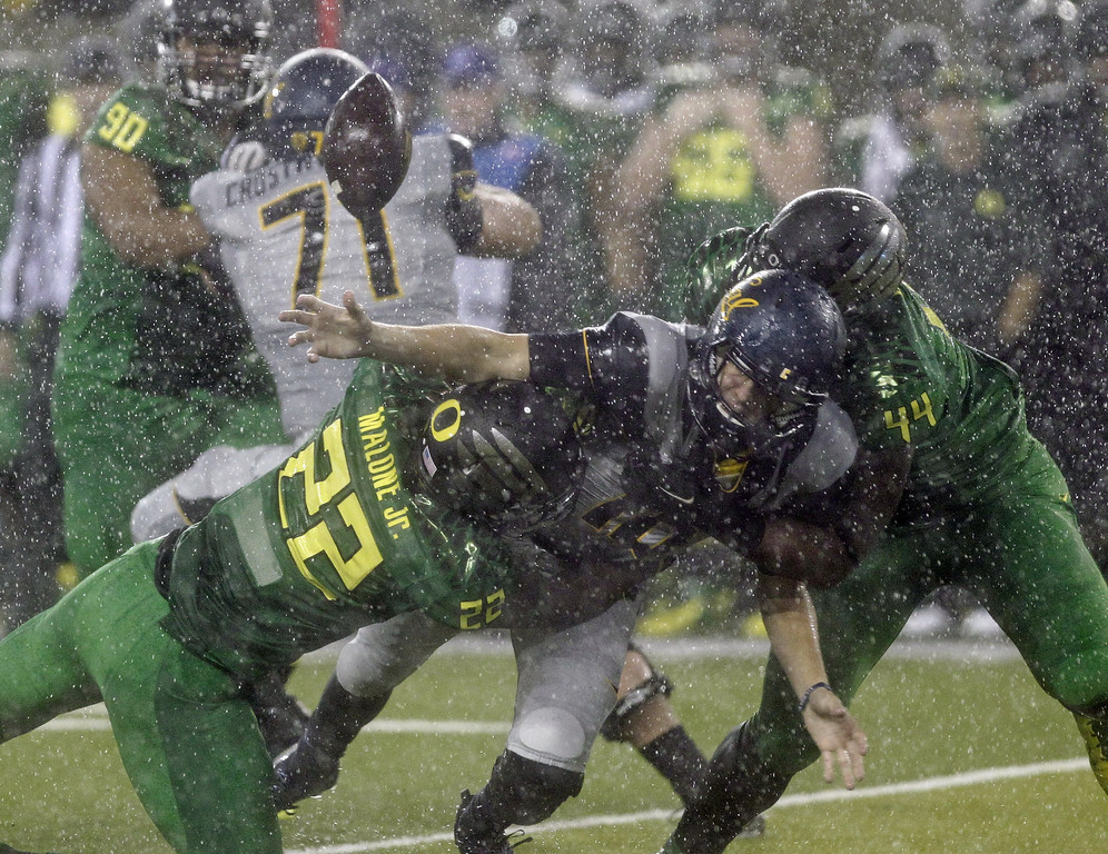. California quarterback Jared Goff, middle, fumbles the ball as he is tackled by Oregon defenders Derrick Malone Jr., left, and DeForest Buckner during the first half of an NCAA college football game in the rain in Eugene, Ore., Saturday, Sept. 28, 2013. (AP Photo/Don Ryan)