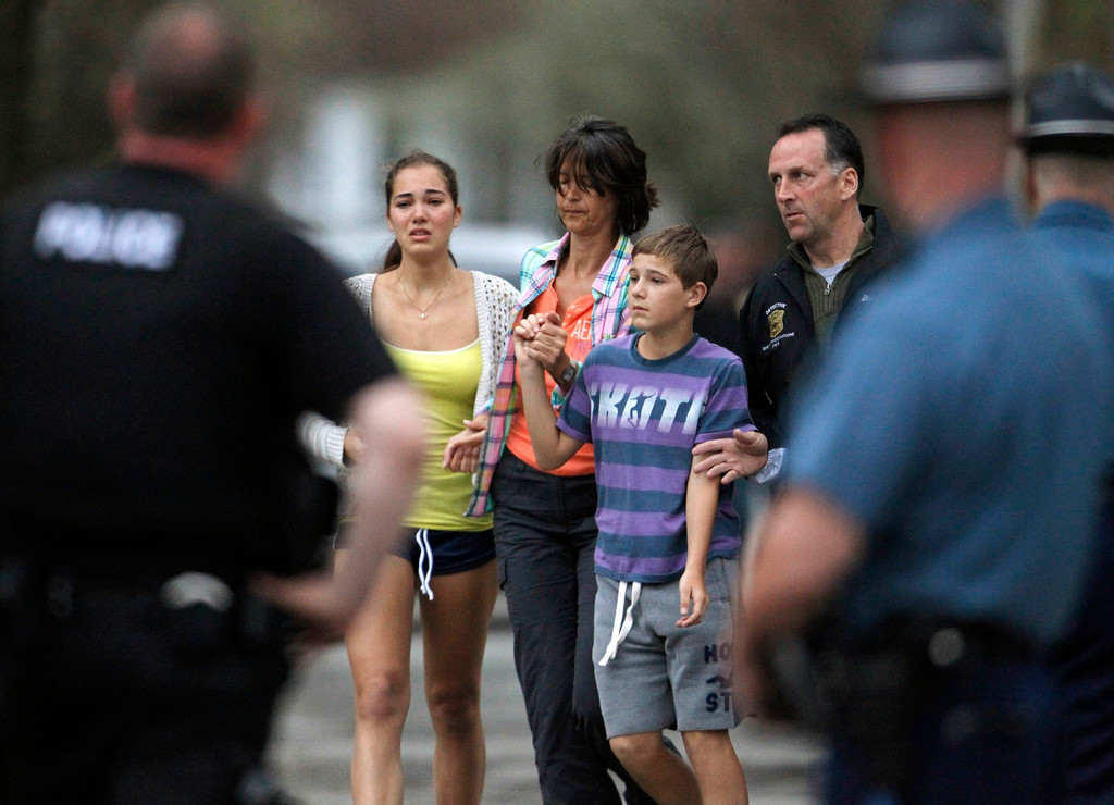 . Police officers escort a family away from their house as police SWAT teams assault a house, firing their weapons on Franklin Street during the search for Dzhokhar Tsarnaev, the surviving suspect in the Boston Marathon bombings, in Watertown, Massachusetts April 19, 2013. The manhunt for Dzhokhar Tsarnaev, 19, one of two brothers believed to have carried out Monday\'s attack, took a dramatic turn just minutes after authorities announced they were lifting a shelter-in-place order imposed on the entire city of Boston. REUTERS/Jim Bourg (UNITED STATES - Tags: CRIME LAW)