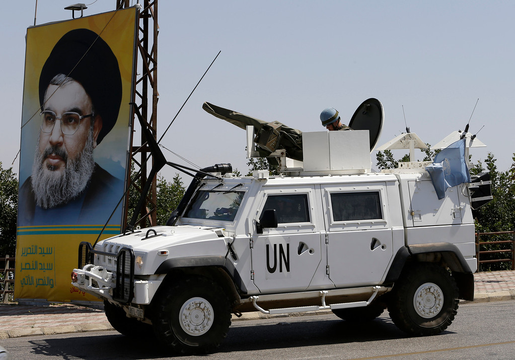 . Spanish U.N peacekeepers, pass a poster of Hezbollah leader Sheik Hassan Nasrallah, as they patrol the Lebanese side of the Lebanese-Israeli border in the southern village of Kfar Kila, Lebanon, Tuesday May 7, 2013. President Bashar Assad\'s regime has given a Palestinian militant group the go-ahead to set up missiles to attack Israel in the wake of recent Israeli airstrikes on the Syrian capital, a spokesman for the group said Tuesday. Israel\'s government has not formally confirmed involvement in the strikes on Syria. However, Israeli officials have said the attacks were meant to prevent advanced Iranian weapons from reaching Lebanon\'s Hezbollah militia, an ally of Syria and foe of Israel. The Israeli settlement of Metulla, is seen at background. (AP Photo/Hussein Malla)