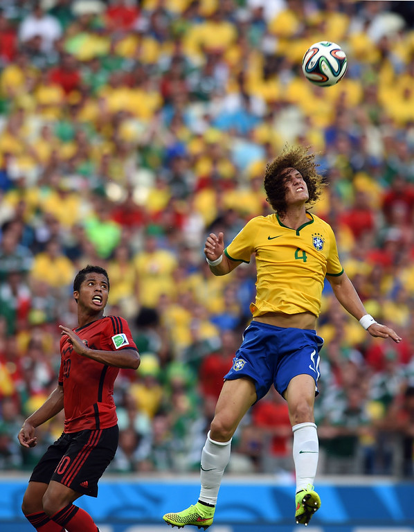 . Brazil\'s defender David Luiz (R) jumps for th eball next to Mexico\'s forward Giovani Dos Santos (L) during a Group A football match between Brazil and Mexico in the Castelao Stadium in Fortaleza during the 2014 FIFA World Cup on June 17, 2014.  (VANDERLEI ALMEIDA/AFP/Getty Images)