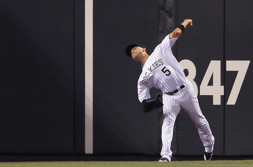 . Left fielder Carlos Gonzalez #5 of the Colorado Rockies fields a double by Tim Federowicz #18 of the Los Angeles Dodgers and makes the throw to the infield in the eighth inning at Coors Field on September 3, 2013 in Denver, Colorado.  (Photo by Doug Pensinger/Getty Images)