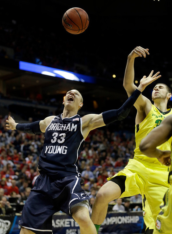 . BYU forward Nate Austin (33) and Oregon forward Ben Carter battle for a rebound during the first half of a second-round game in the NCAA college basketball tournament Thursday, March 20, 2014, in Milwaukee. (AP Photo/Morry Gash)