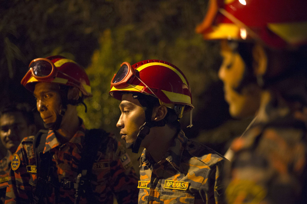 . Malaysian emergency services personnel look on at the scene after a bus carrying tourists and local residents fell into a ravine near the Genting Highlands, about an hour\'s drive from Kuala Lumpur on August 21, 2013.  AFP PHOTO / MOHD RASFAN/AFP/Getty Images