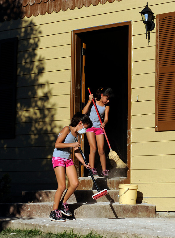 . Twin sisters Abby and Gabby Ramirez, age 10, helped clean out the flooded home of their uncle Horacio Perches in Evans Saturday. Residents of Evans continued the grim work of salvaging personal belongings from flooded homes Saturday afternoon, September 21, 2013.  Photo By Karl Gehring/The Denver Post