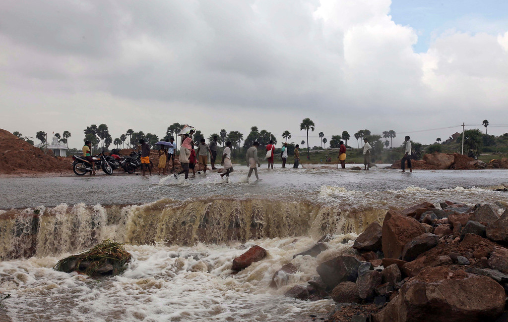 . Indians wade through a flood-damaged road on the outskirts of Hyderabad, in the southern Indian state of Andhra Pradesh, Saturday, Oct. 26, 2013. Days of torrential rains have unleashed floods in the states of Andhra Pradesh and Orissa, killing dozens of people and forced the evacuation of more than 70,000 others from hundreds of low-lying villages. (AP Photo/Mahesh Kumar A.)