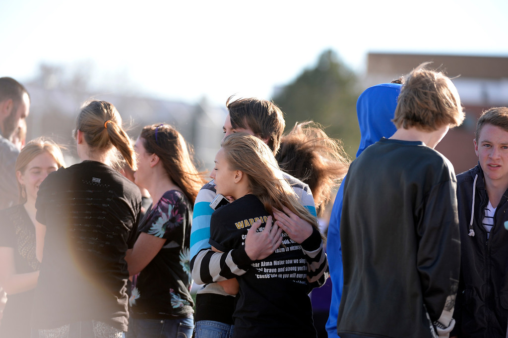 . CENTENNIAL, CO - Students embrace as they stand out side on the football field after a gunman was spotted inside Arapahoe High School December 13, 2013. The gunman was targeting a teacher at the school. The gunman shot two students in the process and then turned the gun on himself. (Photo by John Leyba/The Denver Post)