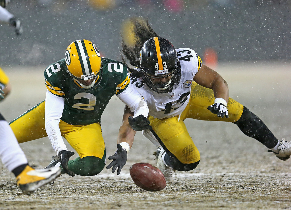 . Mason Crosby #2 of the Green Bay Packers and Troy Polamalu #43 of the Pittsburgh Steelers chase down the ball after a blocked field goal attempt at Lambeau Field on December 22, 2013 in Green Bay, Wisconsin.  The Steelers defeated the Packers 38-31. (Photo by Jonathan Daniel/Getty Images)