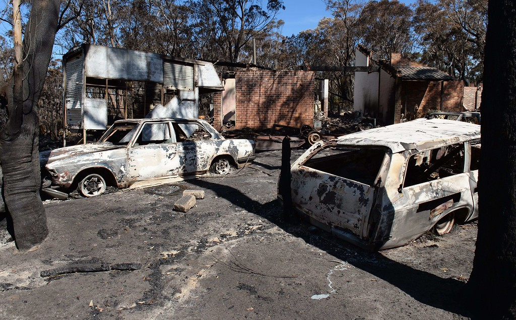 ". Burnt out cars sit in front of a destroyed house at Mount Victoria in the Blue Mountains on October 21, 2013, as volunteer fire brigades race to tame an enormous blaze with officials warning it could merge with others to create a ""mega-fire\"" if weather conditions worsen.   AFP PHOTO/William WEST/AFP/Getty Images"