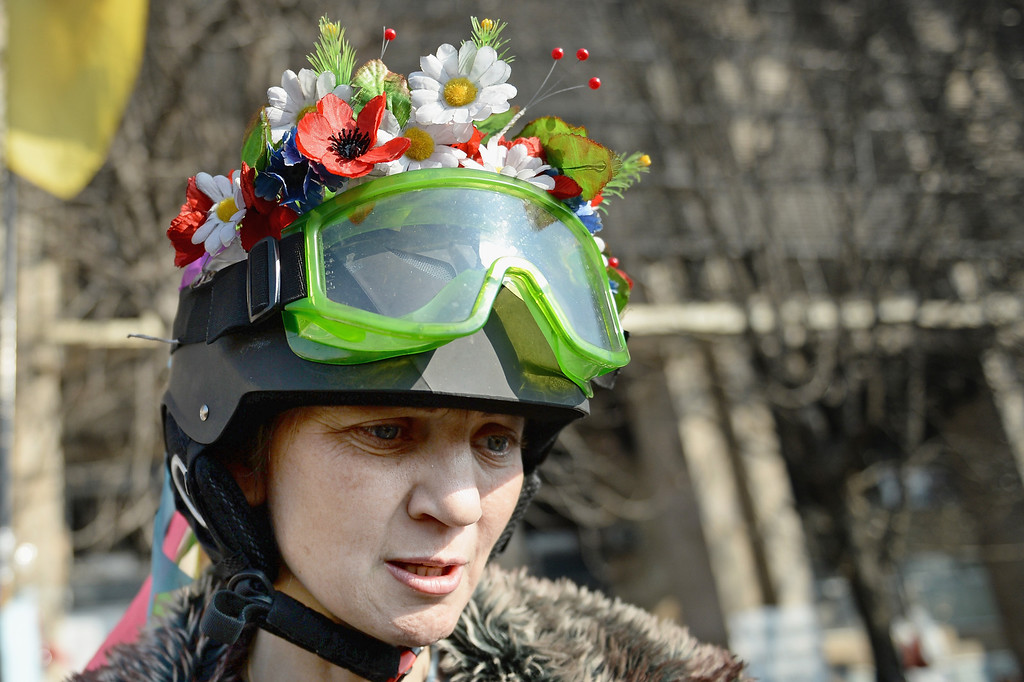 . A female Anti- Government demonstrator wears flowers in her helmet in Independence square, on February 21, 2014 in Kiev, Ukraine. Ukraine\'s president Viktor Yanukovych is thought to have reached a deal with the opposition to end the crisis, after all-night talks in Ukraine mediated by EU foreign ministers.  (Photo by Jeff J Mitchell/Getty Images)